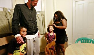 From right, Keena Minifield, with her daughter Gianna, 7, Minifield's fiancee Chris Guido and her son Louis, 8, are shown at their home in York City, Wednesday, Sept. 13, 2017.  With her fiancee serving nine months in York County Prison, Minifield faced tough financial choices. Some weeks, that strain meant deciding between filling up her gas tank or a 20-minute phone call with her imprisoned betrothed.(Dawn J. Sagert /York Dispatch via AP)