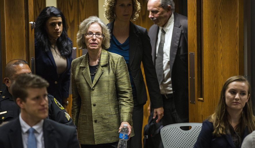 Corinne Miller, former director of the Michigan Bureau of Disease Control Prevention and Epidemiology, enters the courtroom before serving as a witness during the preliminary examination of Nick Lyon, Michigan Department of Health and Human Services director, on Friday, Sept. 22, 2017, in Genesee County District Court in Flint, Mich. Lyon faces charges of involuntary manslaughter and misconduct in office for his response to the Flint Water Crisis. His court preceedings have progressed farther than those of other public officials facing criminal charges in connection to the crisis. Lyon's exam was conducted in front of Judge David J. Goggins. (Terray Sylvester /The Flint Journal-MLive.com via AP)