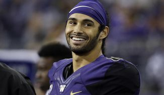 Washington's Dante Pettis smiles as he stands on the sideline late in the second half of an NCAA college football game against Fresno State on Saturday, Sept. 16, 2017, in Seattle. Washington won 48-16. Pettis tied the NCAA career record for punt return touchdowns on a 77-yard return in the first half, the eighth of his career. (AP Photo/Elaine Thompson)