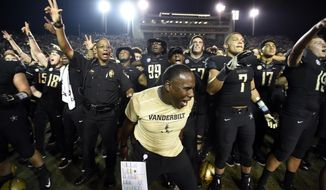 FILE- In this Saturday, Sept. 16, 2017, file photo, Vanderbilt head coach Derek Mason, center, celebrates with players after the team's 14-7 win over Kansas State in an NCAA college football game in Nashville, Tenn. Vanderbilt is off to its best start in years at 3-0 with the latest win an upset of Kansas State. Mason says the key is experience, and he has that. Top-ranked Alabama is up next. (AP Photo/Mark Zaleski, File)