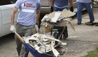 House Speaker Paul Ryan carries a wheel barrow full of debris while assisting Team Rubicon Disaster Response to clean out the Harvey-damaged Garcia house on Lucian Lane Thursday, Sept. 21, 2017, in Friendswood, Texas. Ryan was among a group of Congressional delegates to help Team Rubicon, a non-profit organization that pairs military veterans with first responders to deploy emergency response teams, with relief efforts in the neighborhood. (Yi-Chin Lee/Houston Chronicle via AP)