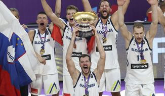 FILE - In this Sept. 17. 2017, file photo, Slovenia's Goran Dragic lifts the trophy after defeating Serbia in the Eurobasket European Basketball Championship finals in Istanbul. Here's how Heat guard Goran Dragic spent his summer vacation. He led Slovenia, his mother's homeland, to an improbable gold medal at the European Championships. (AP Photo/Emrah Gurel, File)