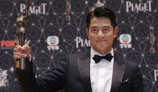 "FILE - In this Sunday, April 3, 2016, file photo, Hong Kong actor Aaron Kwok poses with a trophy after winning the Best Actor award for his movie ""Port of Call"" during the Hong Kong Film Awards in Hong Kong. Kwok, 51, on Friday shared with his fans on his social media page that he was a new father to a newborn infant while not disclosing details of the baby's birth or gender. (AP Photo/Kin Cheung, File)"