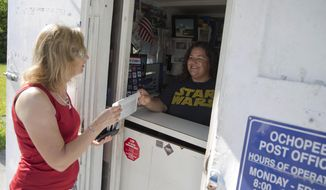 ADVANCE FOR THE WEEKEND OF SEPT. 23-24 AND THEREAFTER - In a June 2, 2016 photo, Ochopee Post Office clerk Shannon Mitchell greets Lioba Zehnter, a German tourist visiting the states as she purchases a postcard to mail back home in Ochopee, Fla. The smallest post office in the United States survived one of the strongest hurricanes ever recorded. (Luke Franke)/Naples Daily News via AP)/Naples Daily News via AP)