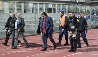 In this photo taken Thursday, Sept. 21, 2017 Sion's President Christian Constantin, center, is escorted by police during the Super League soccer match FC Lugano against FC Sion, at the Cornaredo stadium in Lugano, Switzerland. The senior official with Sion's bid to host the 2026 Winter Olympics has stepped down while being investigated by the Swiss soccer league over a physical confrontation with a television analyst. (Samuel Golay/Ti-Press/Keystone via AP)