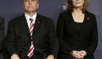 FILE - In this Dec. 10, 2013, file photo, Rutgers athletic director Julie Hermann, right, and head football coach Kyle Flood, listen during an NCAA college football news conference in New York.  The NCAA on Friday, Sept. 22, 2017, has placed Rutgers on two-year probation and publically reprimanded and censured the university for failing to monitor its football program over a five-year period between 2011 and 2015. The NCAA says Rutgers helped itself by cooperating with investigation, firing Flood and Hermann after the 2015 season, and implementing a new drug testing and hiring a new chief medical officer. (AP Photo/Seth Wenig, File)