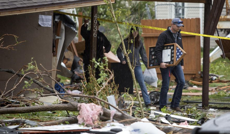 Wesley, right, and Rose Blomquist pull a few personal items out of their tornado damaged home in Washington Terrace, Utah on Friday morning, Sept. 23, 2016. Rose was in the home on Thursday when the tornado hit. She says the last thing she saw was her grill hovering in midair in the backyard before she dived to the kitchen floor. Within a few seconds, her windows exploded and a large tree came down on her roof. ( Benjamin Zack/Standard-Examiner via AP)
