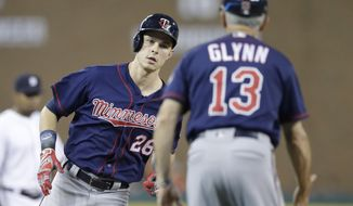 Minnesota Twins' Max Kepler is greeted by third base coach Gene Glynn after a solo home run during the third inning of a baseball game against the Minnesota Twins, Friday, Sept. 22, 2017, in Detroit. (AP Photo/Carlos Osorio)
