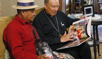 Guatemalan Bishop Julio Edgar Cabrera, right, looks over a Rother Family photo book with Juan Pablo Ixbalan, left, at the Rother Family home in Okarche, Okla, Thursday, Sept. 21, 2017. Stanley Rother, an American priest killed during Guatemala's civil war, is on the path to possible sainthood. Ixbalan knew Rother during his time in Guatemala. A ceremony for Rother's Beatification is scheduled for Saturday, Sept. 23, 2017. (AP Photo/Sue Ogrocki)