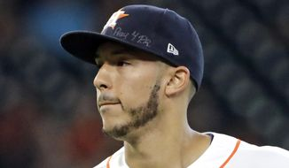 Houston Astros shortstop Carlos Correa wears messages on his cap for those affected by disasters in Mexico and Puerto Rico during the second inning of a baseball game Saturday, Sept. 23, 2017, in Houston. (AP Photo/David J. Phillip)