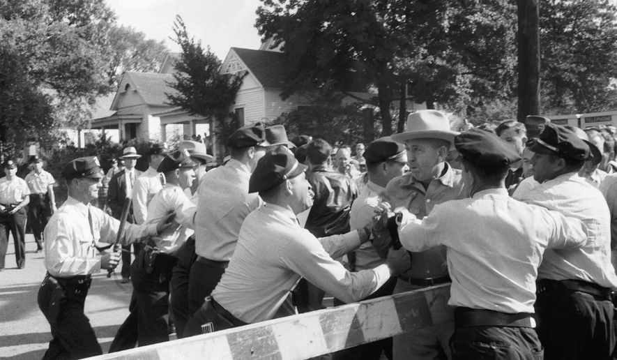 FILE - In this Sept. 23, 1957, file photo, policemen in Little Rock, Ark., work to keep protesters against school integration behind barricades at Central High. Two days later, federal troops sent to the city by President Dwight D. Eisenhower protected nine black students as they entered the school. The 60th anniversary of the Little Rock Nine's enrollment is Monday, Sept. 25,2017. (Will Counts/Arkansas Democrat-Gazette via AP, File)