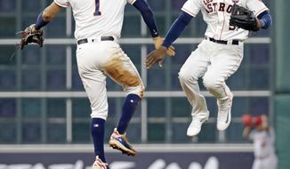 Houston Astros' Carlos Correa (1) and Cameron Maybin (3) celebrate after a baseball game against the Los Angeles Angels Saturday, Sept. 23, 2017, in Houston. The Astros won 6-2. (AP Photo/David J. Phillip)