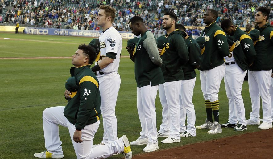 Oakland Athletics catcher Bruce Maxwell kneels during the national anthem before the start of a baseball game against the Texas Rangers Saturday, Sept. 23, 2017, in Oakland, Calif. Bruce Maxwell of the Oakland Athletics has become the first major league baseball player to kneel during the national anthem. (AP Photo/Eric Risberg)