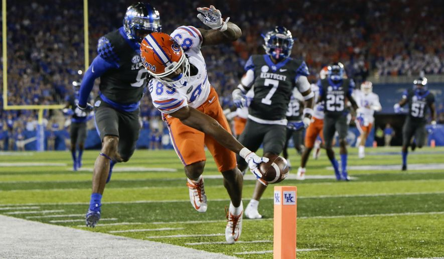 Florida wide receiver Tyrie Cleveland reaches for the goal line in front of Kentucky cornerback Derrick Baity, left, and safety Mike Edwards to score a touchdown during the first half of an NCAA college football game Saturday, Sept. 23, 2017, in Lexington, Ky. (AP Photo/David Stephenson)