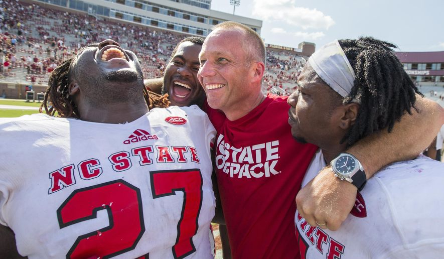 North Carolina State players, from left, Dakwa Nichols (27), defensive tackle B.J. Hill, head coach Dave Doeren and linebacker Jerod Fernandez celebrate defeating Florida State 27-21 in an NCAA college football game in Tallahassee, Fla., Saturday, Sept. 23, 2017. (AP Photo/Mark Wallheiser)