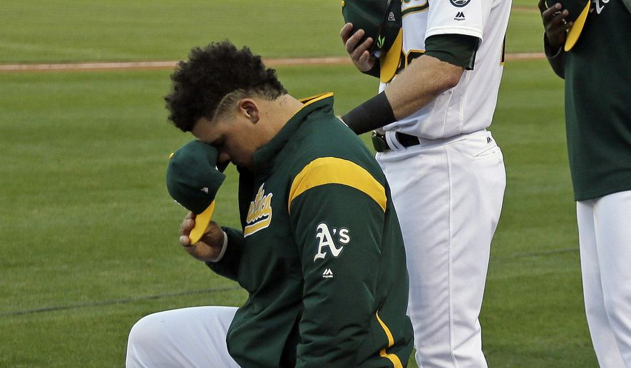 Oakland Athletics catcher Bruce Maxwell, left, kneels as teammate Mark Canha, right, looks on during the National Anthem before the start of a baseball game against the Texas Rangers Saturday, Sept. 23, 2017, in Oakland, Calif. Bruce Maxwell of the Oakland Athletics has become the first major league baseball player to kneel during the national anthem. (AP Photo/Eric Risberg)