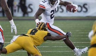 Auburn running back Kerryon Johnson, right, escapes the tackle of Missouri's Thomas Wilson, left, during the first quarter of an NCAA college football game Saturday, Sept. 23, 2017, in Columbia, Mo. (AP Photo/L.G. Patterson)