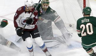 Minnesota Wild goalie Devan Dubnyk, center, stirs up an ice cloud as he stops a shot behind Colorado Avalanche's Dominic Toninato, left, during the first period of a NHL preseason hockey game, Saturday, Sept. 23, 2017, in St. Paul, Minn. (AP Photo/Jim Mone)