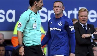 Everton's Wayne Rooney, centre, confronts one of the assistant referees as team manager Ronald Koeman watches, during the English Premier League soccer match between Everton and Bournemouth, at Goodison Park, Liverpool, England, Saturday Sept. 23, 2017. (Barrington Coombs/PA via AP)