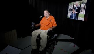 In this Tuesday, Sept. 19, 2017 photo,  Marc Buoniconti talks during an interview in New York. On the right is a photograph of the former Citadel player with his father, Nick Buoniconti. Buoniconti wants to see youth football banned. A former college player who was paralyzed during a game and now a spokesman for the Miami Project, Buoniconti believes children's brains are put in jeopardy with every hit.  (AP Photo/Mark Lennihan)