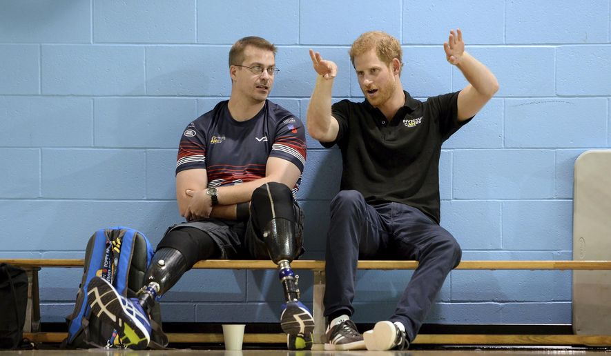 Britain's Prince Harry, right, speaks to an athlete from the volleyball team from the United Kingdom during training in the lead-up to the Invictus Games, in Toronto on Friday, Sept. 22, 2017. THE CANADIAN PRESS/Nathan Denette/The Canadian Press via AP)