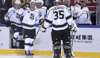 Members of the Los Angeles Kings celebrate with goalie Darcy Kuemper (35) after winning their NHL China exhibition game against the Vancouver Canucks at the Cadillac Arena in Beijing, Saturday, Sept. 23, 2017. The Kings won 4-3 in an overtime shootout. (AP Photo/Mark Schiefelbein)