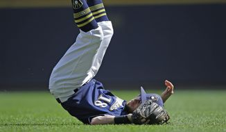 Milwaukee Brewers' Eric Sogard flips over as he watches his throw to first base to complete a double play of a ball hit by Chicago Cubs' Anthony Rizzo at first during the third inning of a baseball game Saturday, Sept. 23, 2017, in Milwaukee. (AP Photo/Jeffrey Phelps)