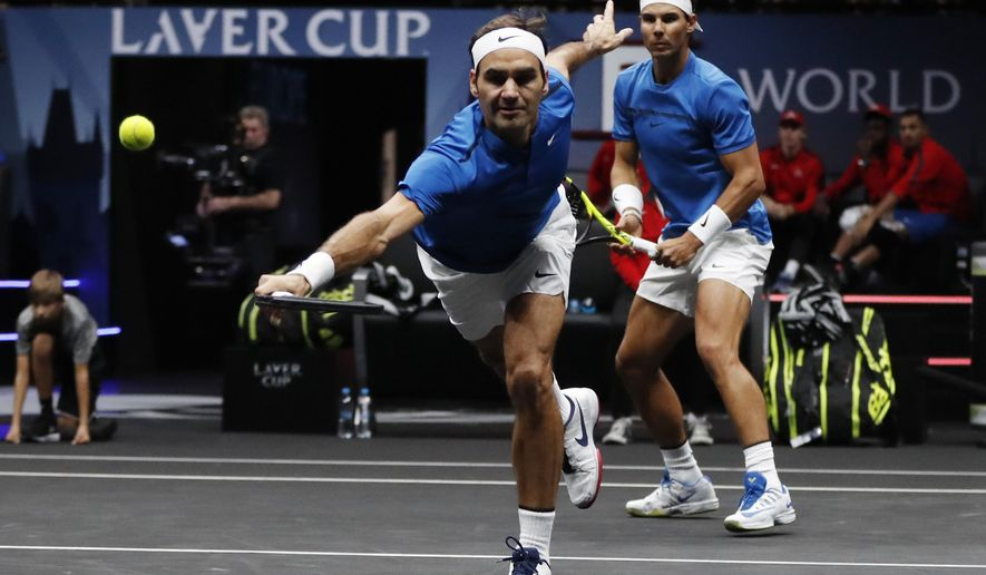 Europe's Rafael Nadal, right, watches his teammate Roger Federer, left, returning a ball to World's Jack Sock and Sam Querrey during their Laver Cup doubles tennis match in Prague, Czech Republic, Saturday, Sept. 23, 2017. (AP Photo/Petr David Josek)
