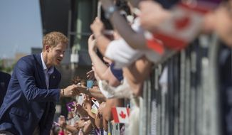 Prince Harry greets a waiting crowd as he visits The Centre for Addiction and Mental Health in Toronto on Saturday, Sept. 23, 2017.  (Chris Young/The Canadian Press via AP)