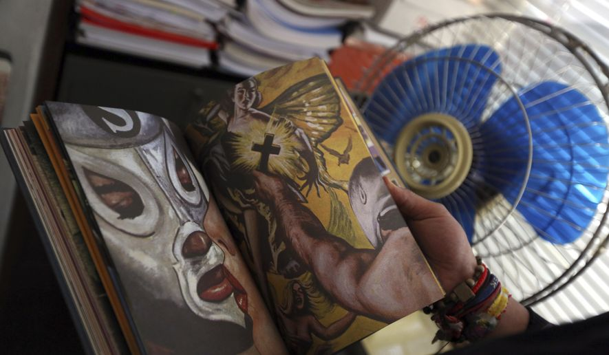 In this Sept. 12, 2017 photo, Roberto Shimizu leafs through pages of an El Santo comic book at the Old Toy Museum in Mexico City. The comic books fed from the stories sent from fans that wanted El Santo to fight characters like mummies, lady vampires or nazis. (AP Photo/Gustavo Martinez Contreras)