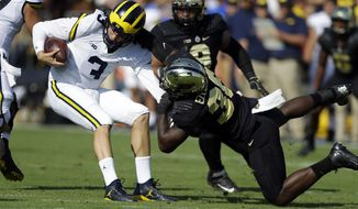 Michigan quarterback Wilton Speight (3) is sacked by Purdue linebacker Danny Ezechukwu (36) during the first half of an NCAA college football game in West Lafayette, Ind., Saturday, Sept. 23, 2017. (AP Photo/Michael Conroy)