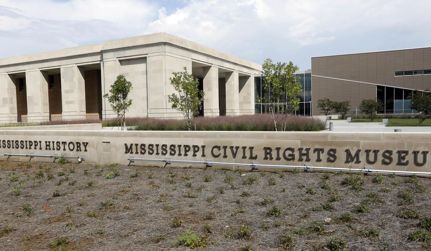 Signage promoting the two new Mississippi history museums rests before the Museum of Mississippi History, left, and the Mississippi Civil Rights Museum, Friday, Sept. 22, 2017, in Jackson, Miss. The facilities are in the process of preparing exhibits for placement in the two buildings. (AP Photo/Rogelio V. Solis)