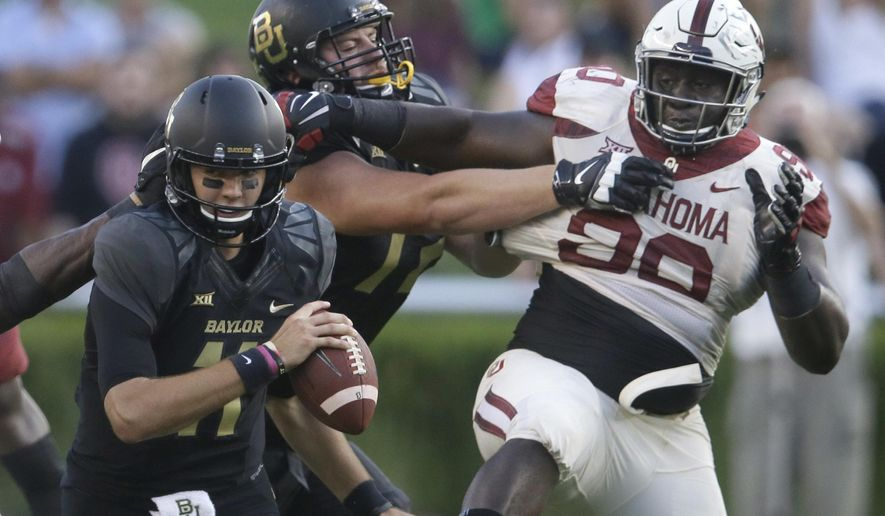 Baylor quarterback Zach Smith (11) turns as teammate offensive lineman Blake Blackmar (72) blocks Oklahoma defensive tackle Neville Gallimore (90) during the first half of an NCAA college football game in Waco, Texas, Saturday, Sept. 23, 2017. (AP Photo/LM Otero)