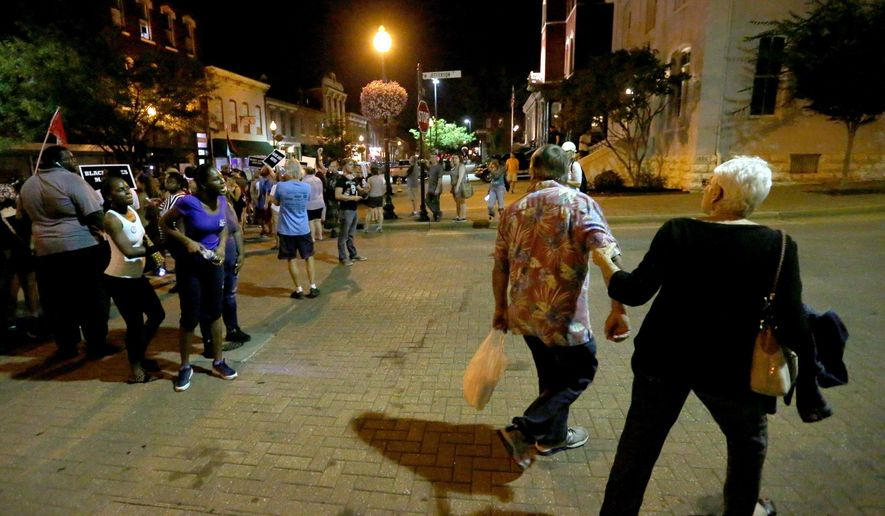 A man is pulled away from yelling at protesters as they rally over the recent the acquittal of a white former police officer, Jason Stockley, in the killing of a black man, Anthony Lamar Smith, who was a drug suspect, in St. Charles, Mo., Friday, Sept. 22, 2017. Nearly 150 protesters gathered outside the St. Louis Outlet Mall in Hazelwood, but the mall and all its stores had closed early because of the planned demonstrations. Organizers had everyone carpool to nearby St. Charles, which was overrun with thousands of people attending an Oktoberfest event. (Christian Gooden/St. Louis Post-Dispatch via AP)