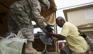 National Guard personnel evacuate Toa Ville resident Luis Alberto Martinez after the passing of Hurricane Maria, in Toa Baja, Puerto Rico, Friday, September 22, 2017. Because of the heavy rains brought by Maria, thousands of people were evacuated from Toa Baja after the municipal government opened the gates of the Rio La Plata Dam. (AP Photo/Carlos Giusti)