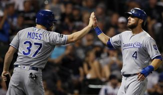 Kansas City Royals' Alex Gordon, right, celebrates scoring a run against the Chicago White Sox with teammate Brandon Moss during the seventh inning of a baseball game Saturday, Sept. 23, 2017, in Chicago. (AP Photo/Jim Young)