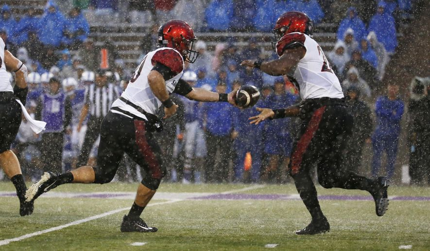 San Diego State quarterback Christian Chapman (10) hands off to Rashaad Penny (20) in the rain during the first half of an NCAA college football game against Air Force, Saturday, Sept. 23, 2017, at Air Force Academy, Colo. (AP Photo/Jack Dempsey)