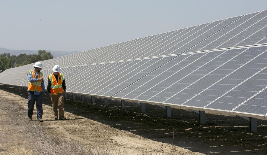 FILE - In this Aug. 17, 2017, file photo, solar tech Joshua Valdez, left, and senior plant managerTim Wisdom walk past solar panels at a Pacific Gas and Electric Solar Plant, in Dixon, Calif. Cheap solar panels imported from China and other countries have led to a boom in the U.S. solar industry, where rooftop and other installations have surged 10-fold since 2011. But two U.S. solar manufacturing companies say the flood of imports has led one to bankruptcy and forced the other to lay off three-quarters of its workforce. (AP Photo/Rich Pedroncelli, File)