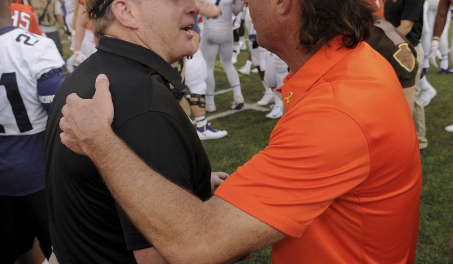 Oklahoma State head coach Mike Gundy congratulates TCU head coach Gary Patterson for his win in Stillwater, Okla., Saturday, Sept. 23, 2017. TCU defeated Oklahoma State 44-31.(AP Photo/Brody Schmidt)
