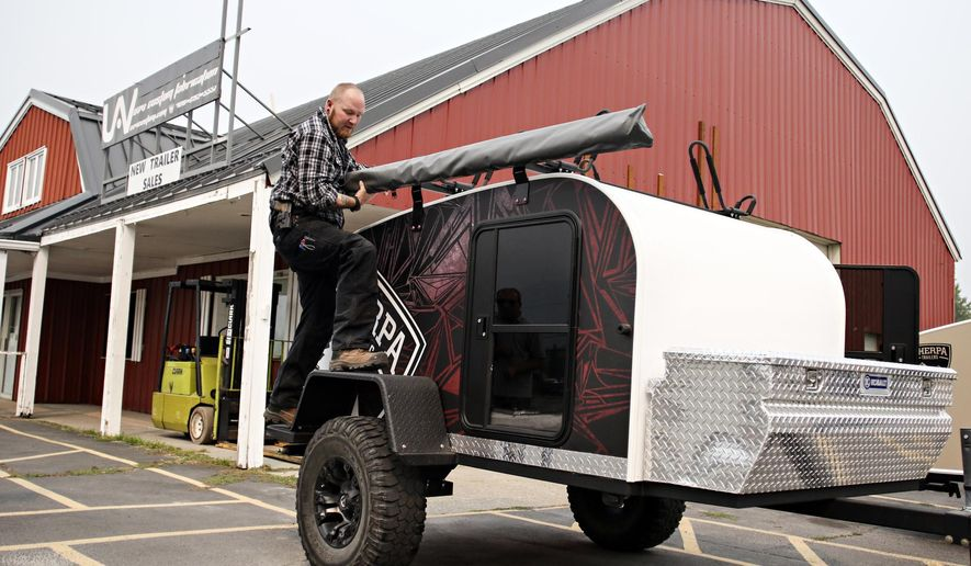 In a Sept. 6, 2017 photo,Adam Montgomery shows the versatility of Sherpa Trailers' Offroad model, a 5-by-8-foot off-road trailer with 31-inch tires and full suspension, at the shop in Libby, Mont. Three years after opening up shop, the three partners at Sherpa Trailers and two full-time employees are busy selling trailers across the Pacific Northwest and as far east as Illinois. (Greg Lindstrom/Flathead Beacon via AP)