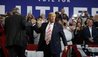 President Donald Trump, center, greets U.S. Senate candidate Luther Strange after speaking at a campaign rally, Friday, Sept. 22, 2017, in Huntsville, Ala. (AP Photo/Evan Vucci)