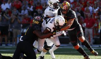 Central Florida running back Taj McGowan, center, rushes for a touchdown past Maryland linebackers Jermaine Carter Jr., left, and Shane Cockerille, right, in the first half of an NCAA college football game in College Park, Md., Saturday, Sept. 23, 2017. Also pictured is Central Florida offensive lineman Aaron Evans (66). (AP Photo/Patrick Semansky)