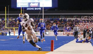 Virginia running back Olamide Zaccheaus (4) scores a touchdown during the second half of an NCAA college football game against Boise State in Boise, Idaho, Friday, Sept. 22, 2017. Virginia won 42-23. (AP Photo/Otto Kitsinger)