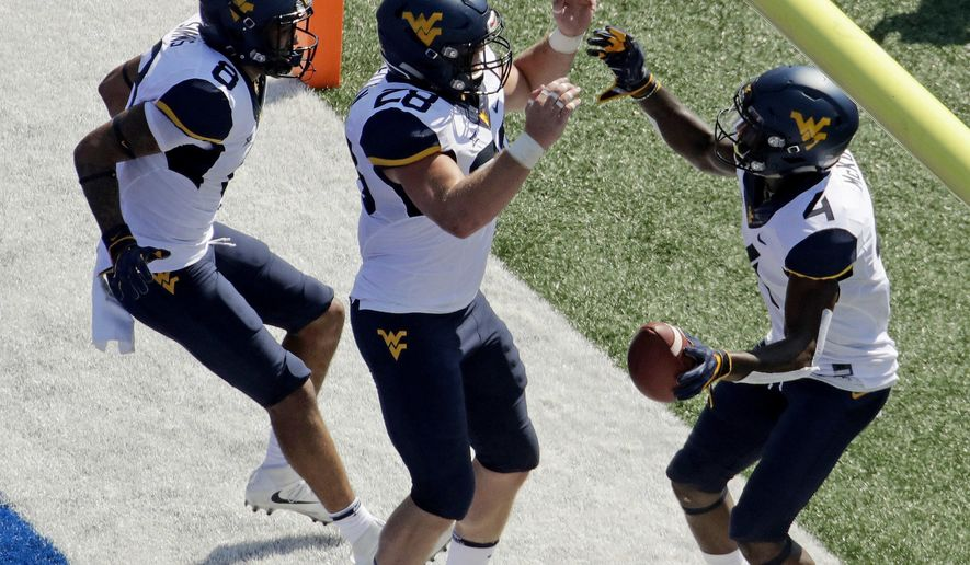 West Virginia running back Kennedy McKoy (4) celebrates with tight end Elijah Wellman (28) and wide receiver Marcus Simms (8) after scoring a touchdown during the first half of an NCAA college football game against Kansas Saturday, Sept. 23, 2017, in Lawrence, Kan. (AP Photo/Charlie Riedel)