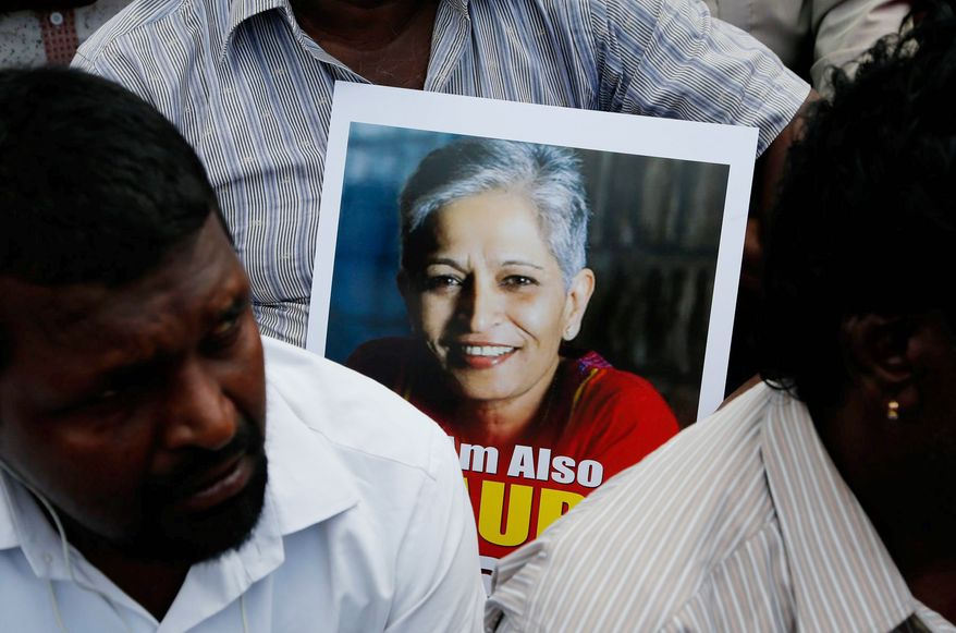 A poster of slain Indian journalist Gauri Lankesh is shown held by a protester at a recent vigil.    Associated Press photo