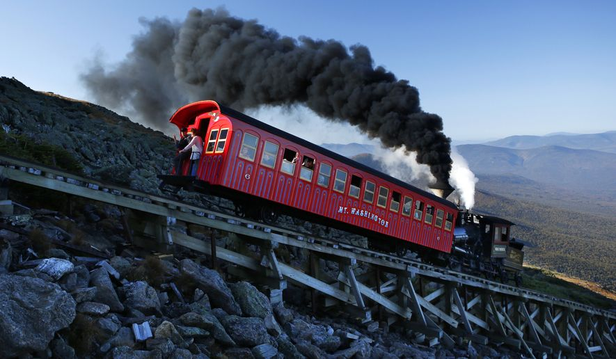 A vintage coal-fired steam engine pushes a passenger car up the Cog Railway on a 3.8-mile journey to the summit of 6,288-foot Mount Washington in New Hampshire, Sunday, Sept. 24, 2017. Tourists visiting the northeast's highest peak were rewarded with summer-like weather on the first weekend of autumn. (AP Photo/Robert F. Bukaty)