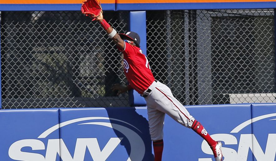 Washington Nationals right fielder Victor Robles (14) hauls in a fly ball hit by Jose Reyes during the first inning of a baseball game against the New York Mets, Sunday, Sept. 24, 2017, in New York. (AP Photo/Kathy Willens) ** FILE **
