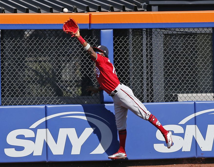 Washington Nationals right fielder Victor Robles (14) hauls in a fly ball hit by Jose Reyes during the first inning of a baseball game against the New York Mets, Sunday, Sept. 24, 2017, in New York. (AP Photo/Kathy Willens)