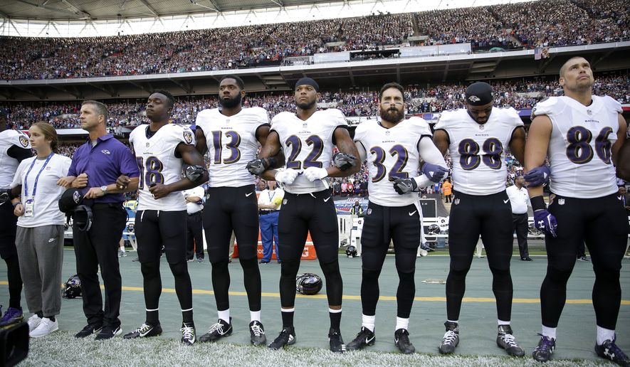 Baltimore Ravens head coach John Harbaugh, second from left, links arms with his daughter Alison, left, and players during the playing of the U.S. national anthem before an NFL football game against the Jacksonville Jaguars at Wembley Stadium in London, Sunday Sept. 24, 2017. (AP Photo/Matt Dunham)