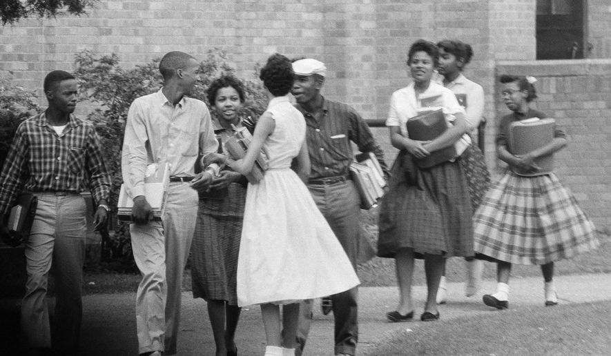 FILE - In this Oct. 2, 1957, file photo, the first black students to enroll at Central High School in Little Rock, Ark., leave the building and walk toward a waiting Army station wagon following their classes. Monday, Sept. 25, 2017, marks the 60th anniversary of when nine black students enrolled at the Arkansas school. One of the nine students is obscured by another student in this photograph. (AP Photo/Ferd Kaufman, File)